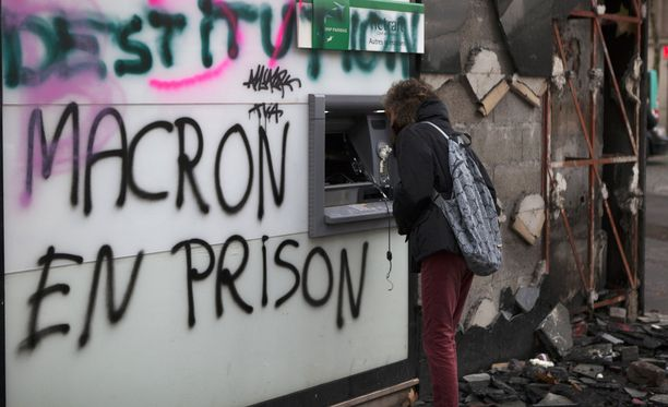 Muun muassa pankkiautomaatit on tuhrittu Champs-Élysées -kadulla Pariisissa presidentti Macronia vastustavilla graffiteilla.