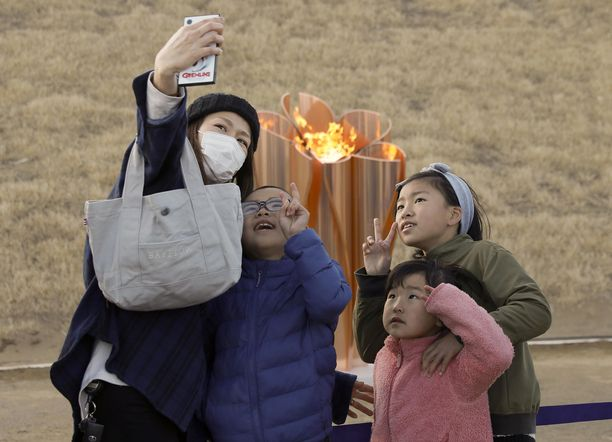Perhe ottaa kuvaa olympiatulen edessä. Olympiatuli saapui Japaniin perjantaina.