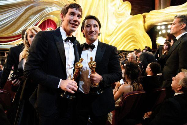 Alex Honnold turvallisesti maan kamaralla ja Oscar-palkinto käsissään. Oikealla Free Solo -dokumentin ohjaaja Jimmy Chin.