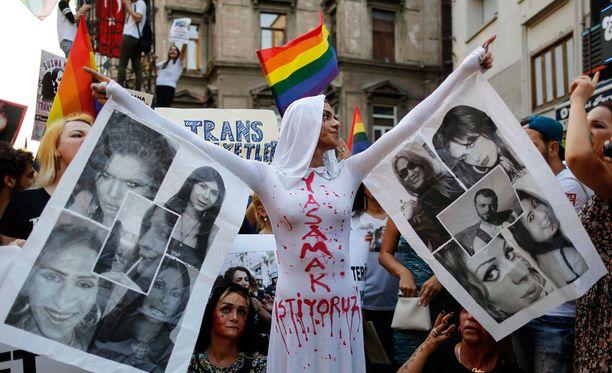 Mielenosoittajat maalasivat itselleen verisiä kyyneleitä ja veritahroja mielenosoituksessa.