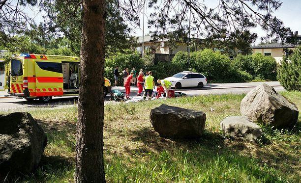Ensihoitajat hoitivat onnettomuuden uhria tapahtumapaikalla.