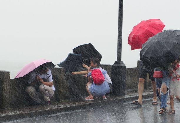 Kiina, Hangzhou. Ihmiset taistelevat nousevaa myrskytuulta vastaan.