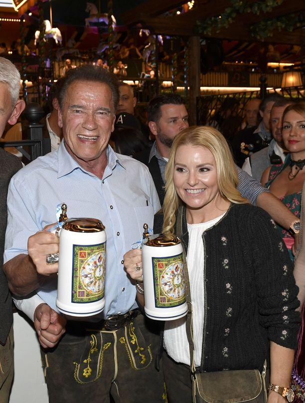 Olutta, nahkahousuja, ja kunnon juhlatunnelmaa. Arnold Schwarzenegger nauttii Heather Milliganin kanssa Oktoberfestien tunnelmasta.