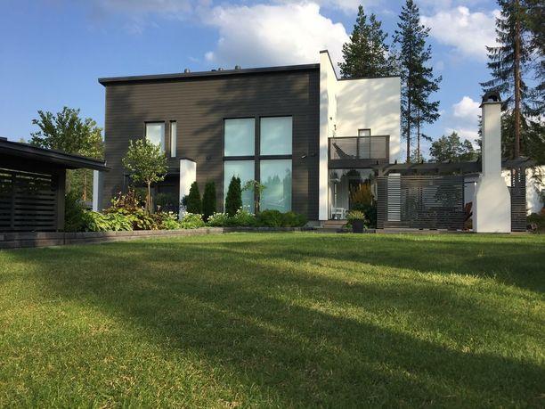 Tumman puutalon ulkoverhousta on maustettu valkoisella rappauksella. Koti on yksi Seinäjoen asuntomessualueen kohteista.