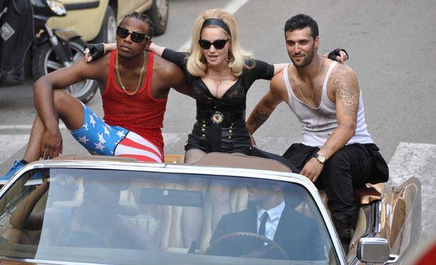 Madonna pääsi istuskelemaan kahden miestanssijan väliin.