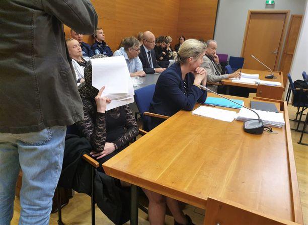 Nuori nainen myönsi oikeussalissa keränneensä kuusesta oksia poltettavaksi ruumiin palopaikalle. Kuvassa hän on suojautunut huivilla ja paperipinolla.