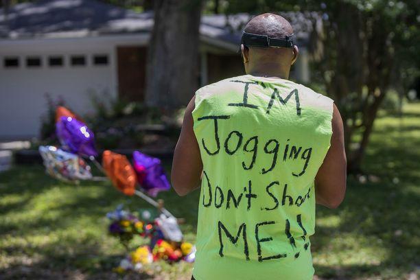 """Miehen selässä lukee: """"Olen lenkillä, älkää ampuko minua!"""" Kuva otettu Arbeyn muistomerkillä toukokuussa 2020."""