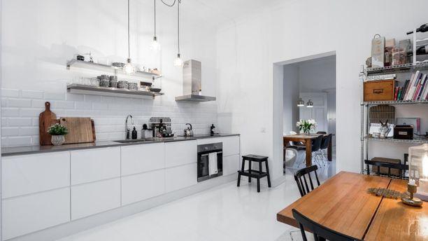 Tässäkin keittiössä huomaa, miten puisilla kalusteilla vaalea tila saa lämpöä.