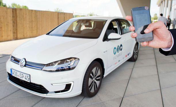 Mies käyttää älypuhelinta ohjatakseen kuljettajatonta Volkswagen E-Golfia parkkipaikalle.