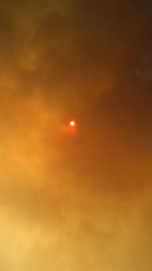 Aurinko pilkisti valtavan sakean savupilven takaa.