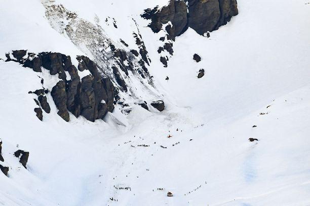 Pelastajat yrittivät kaivaa uhreja esiin lumen alta iltapäivällä.
