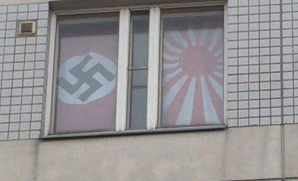 Kansallissosialistisen Saksan sekä Japanin keisarikunnan vanha sotalippu roikkuvat opiskelija-asunnon ikkunassa.