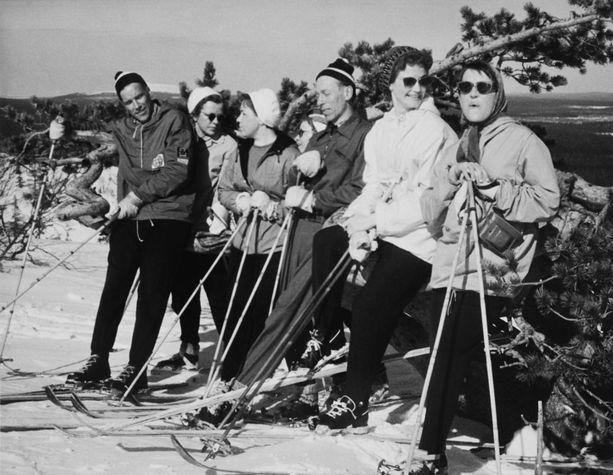 Säästöpankkien henkilökunta matkasi virkistysretkelle Pyhätunturille vuonna 1958. Seurue poseerasi hiihtoasuissa auringonpaisteessa.