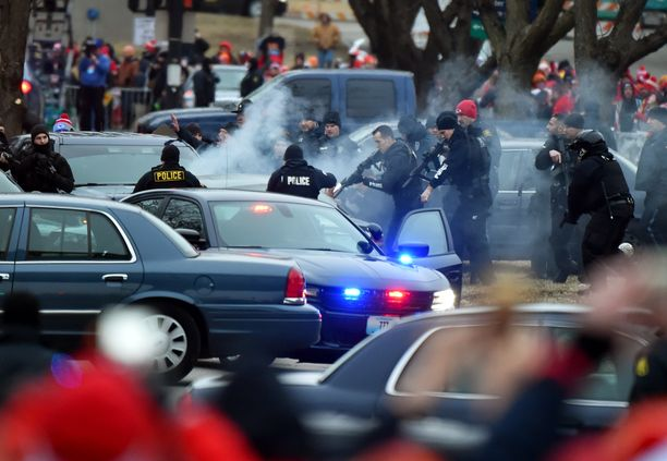 Poliisit lähestyivät pakoautoa aseet pystyssä.