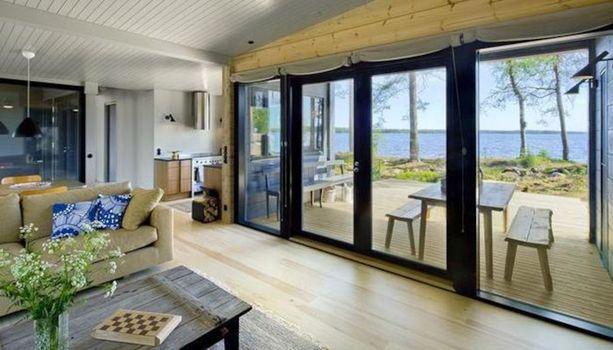 Mäntyharjulla sijaitsevan hirsitalon ikkunoista siintävät järvimaisemat.