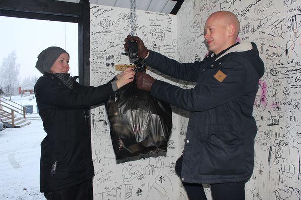 Kunnanjohtaja Juha Viitasaari ja 4H-yhdistyksen toiminnanjohtaja Saija Källi punnitsivat muoviroskien määrää. Palautuspisteen seinissä Soinin kunnan 150-vuotisjuhlaan liittyviä tervehdyksiä.