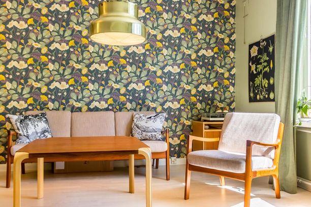 Retroilu on nyt sallittua! Näyttävä kukkatapetti on muodikas valinta. Lisäpisteitä trendikkyyteen tuovat kellertävä ja lämmin sävymaailma sekä 50- ja 60-luvun tyyliset vanhat huonekalut.