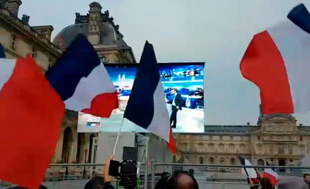 anskan liput riehuvat vimmatusti Louvren lasipyramidin edessä kun ensimmäiset tulokset paljastivat Macronille 65 prosentin äänisaaliin.