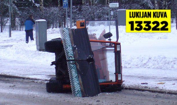 Aurausauto makasi kyljellään tien sivussa.