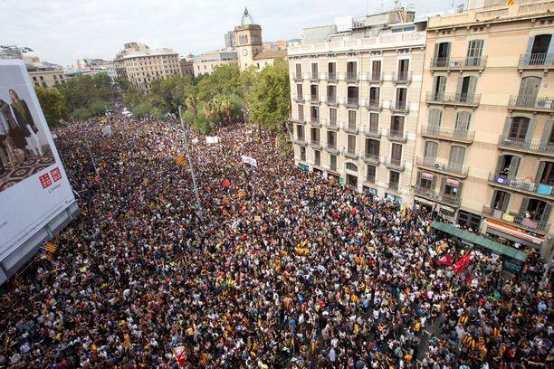 Ihmiset osoittavat mieltään Barcelonan keskustan Katalonia-aukiolla.