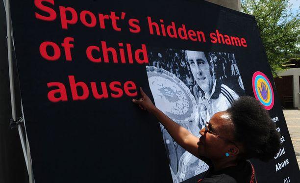 Lastenoikeusaktivisti ripusti julistetta oikeustalon ulkopuolelle ennen Bob Hewittin oikeudenkäynnin alkua Johannesburgissa.