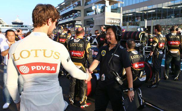 Kuljettaja Romain Grosjean ja kilpainsinööri Ayao Komatsu kättelivät Abu Dhabissa marraskuussa.