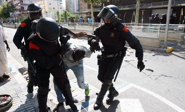 Espanjan mellakkapoliisi pidättämässä maahanmuuttajaa mielenosoituksessa. Espanjan hallitus perustelee uutta lakia väkivaltaisuuksien hillitsemisellä.