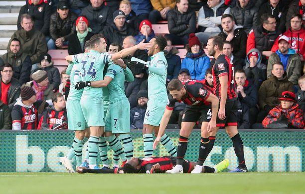Bournemouthin Jefferson Lerma harmitteli nurmen pinnassa omaa maaliaan samalla, kun Arsenal-pelaajat juhlivat sitä.