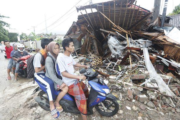 Paikalliset asukkaat katsovat tsunamin aiheuttamia tuhoja.