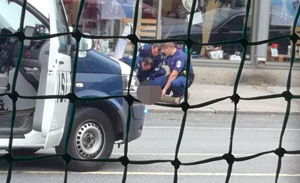 Ihmiset potkivat ja löivät puukottajaa päähän ja ylävartaloon. Kuvassa poliisit ovat kerääntyneet epäillyn ympärile.