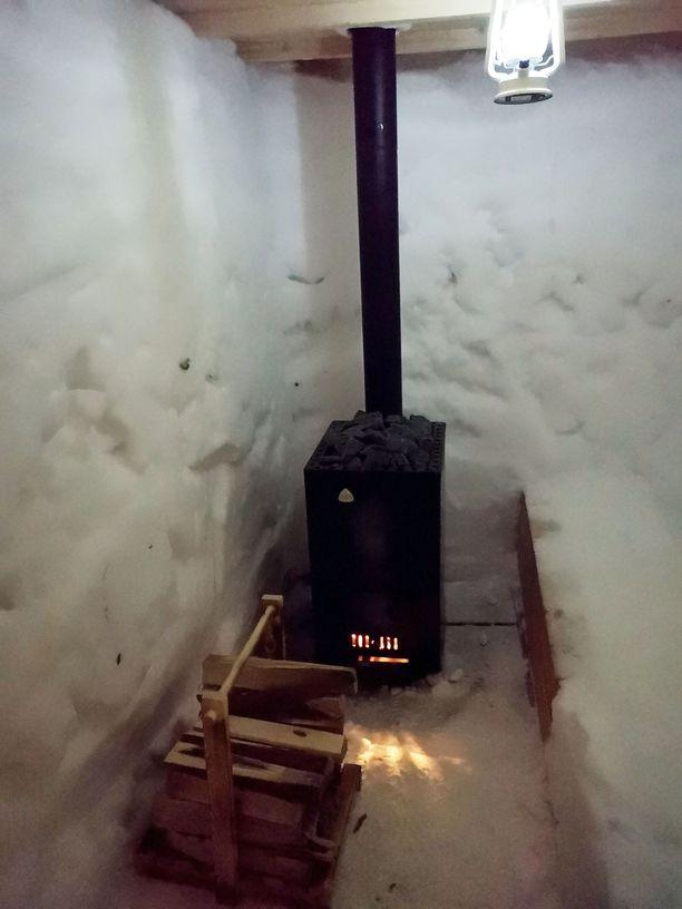 Kiuas lämpenemässä. Lumisauna ei sula, jos saunoja malttaa lopettaa ajoissa touhunsa.