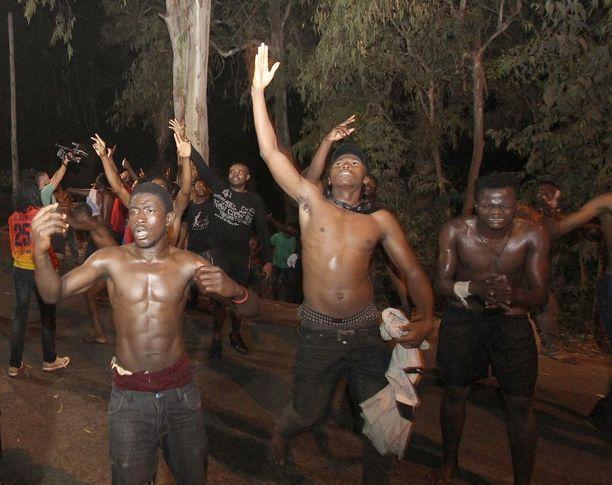Siirtolaiset juhlivat päästyään Espanjan puolelle varhain maanantaiaamuna.