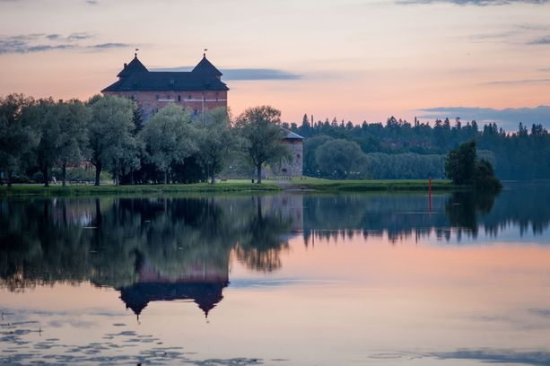 Hämeen linna heijastuu tyyneen järveen.