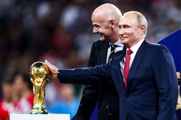 Fifa-pomo Gianni Infantino (vas.) antoi Vladimir Putinin hivellä MM-pokaalia.
