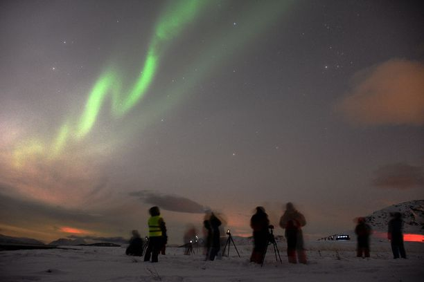 Kansainvälinen turistijoukko ihmetteli revontulia Jäämeren rannalla.