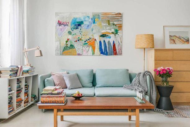 Miten värit tuodaan sisustukseen? Taulu tai taulut ovat yksi helppo keino. Taulu voi olla jo yksinään huoneen väriläiskä ja katseenvangitsija. Voit myös napata taulusta ne kauneimmat värit, joita ripottelet huoneen muuhun sisustukseen, kuten sohvatyynyihin tai mattoon. Kuvan taulu on Eva Lampun.