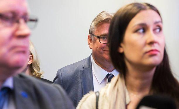 """Uusi vaihtoehto -eduskuntaryhmän """"rivijäsen"""" Timo Soini myhäili tiistain tiedotustilaisuudessa työministeri Jari Lindströmin ja kansanedustaja Tiina Elovaaran takana."""