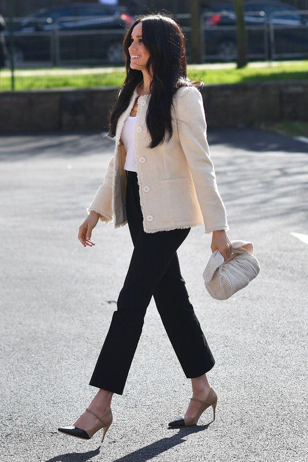 Meghan edusti ME + EM -merkin jakussa, mustissa housuissa ja sievissä korkkareissa. Rejina Pyon laukku tuo asuun trendikkään lisän.