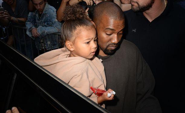 Kanye West kantoi tyttärensä turvaan kuvaajilta muotinäytöksen jälkeen.