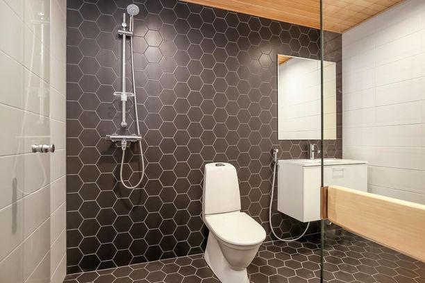 Asunnon kylpyhuone on laatoitettu näyttävästi.