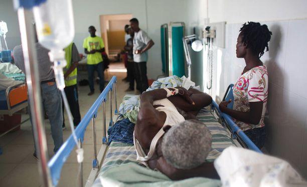 Loukkaantunut makaa sairaalassa Haitissa hurrikaanin jälkeen.