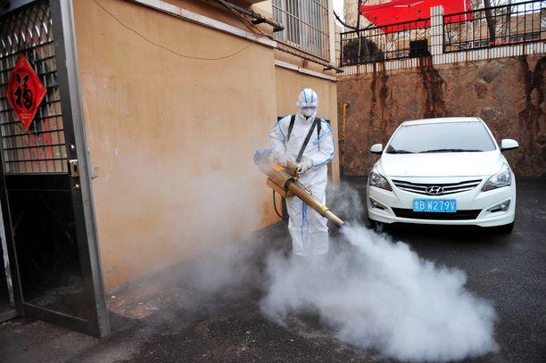 Vapaaehtoinen desinfioi asuinaluetta kiinalaisessa Qingdaon kaupungissa tiistaina. Kiinan hallinto on etsinyt ennalta ehkäiseviä keinoja, joiden avulla yritetään estää koronavirusta leviämästä.