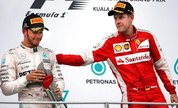 Sebastian Vettel lohdutti palkintojenjaossa toiseksi tullutta Lewis Hamiltonia.