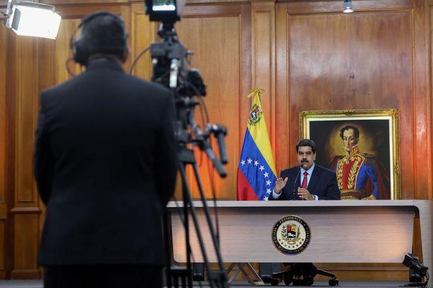 Nicolas Maduron mukaan USA yrittää tukea vallankaappausta, varastaa öljyt ja tuhota bolivariaanisen perinteen. Taustalla oleva maalaus esittää Simon Bolivaria.