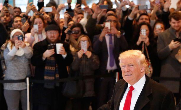 Trumpin poistuessa New York Timesin toimituksesta ihmismassat ottavat hänestä kuvia.