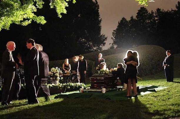 Perheenjäseniä ja sukulaisia arkun ympärillä Arlingtonin sankarihautausmaalla.