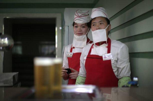 Olutbaarin tarjoilijat Kim Yon Hui (vasemmalla), 29, ja Yang Pok Yong, 42, palvelevat asiakkaiden ohella omien sanojensa mukaan myös johtajaansa.