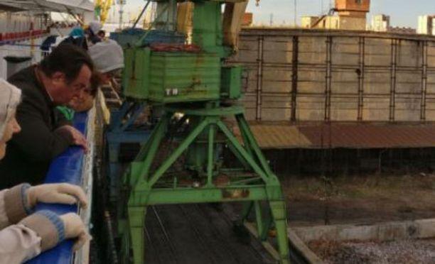 Matkustajia laivan kannella katselemassa epäonnista satamasta lähtöä.