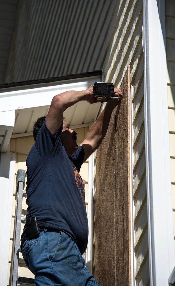 David Baratta tukki ikkunoitaan Carolina Beachissa. Hurrikaanin odotetaan iskevän USA:n itärannikolle perjantaina Suomen aikaa.