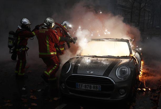 Pelastajat sammuttivat palavaa autoa Pariisissa lauantaina.